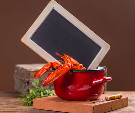 lobster pot: Red lobster in red pot, blackboard on background