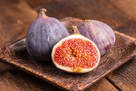 Fresh fruits, figs on the wooden plate Standard-Bild
