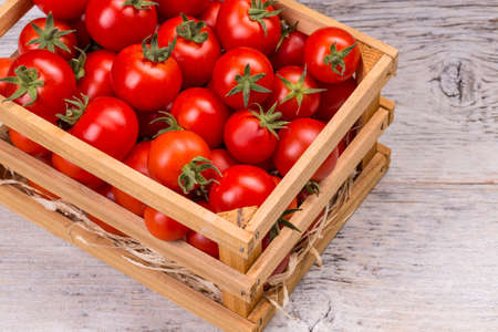 wooden crate: Fresh ripe cherry tomatoes in wooden crate Stock Photo