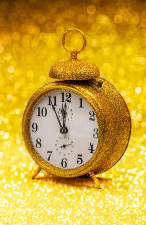 twelve: Vintage alarm clock showing five to twelve