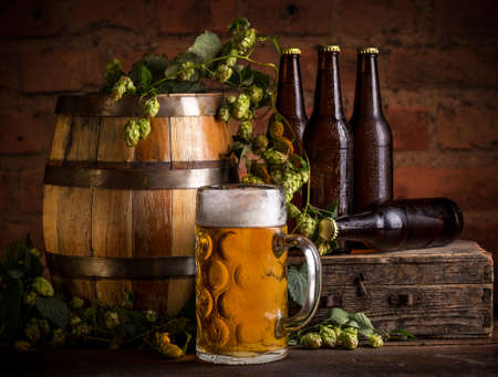 Glass of beer, old oak barrel and hops on wooden table. Stock Photo