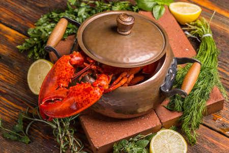 lobster pots: Boiled lobster in copper pot on rustic background