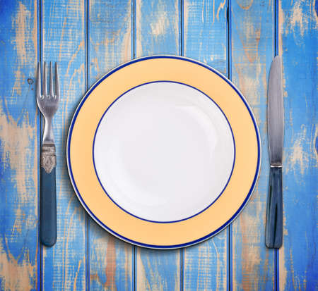 antique dishes: Top view of empty plate and blue vintage cutlery on blue wooden board