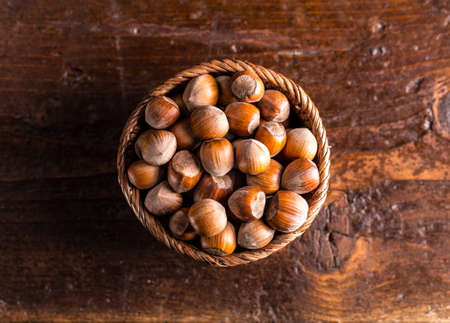 hazelnuts: Top view of hazelnuts in rustic wooden bowl Stock Photo