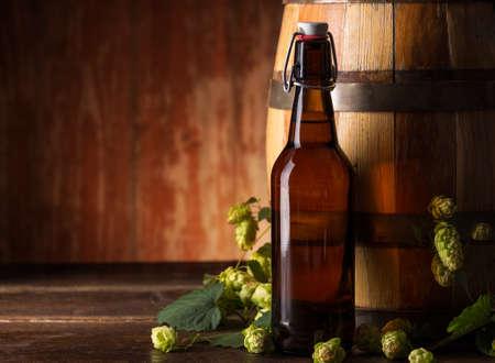 Beer bottles with beer barrel and fresh hops