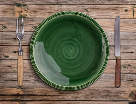 surface view: Empty green plate on a wooden table
