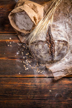 A rustic loaf of sourdough bread on wooden background