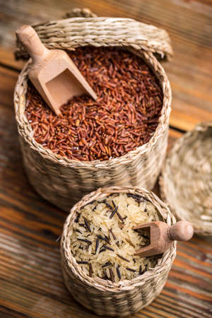 basket: Rice in wicker basket with wooden spoon Stock Photo