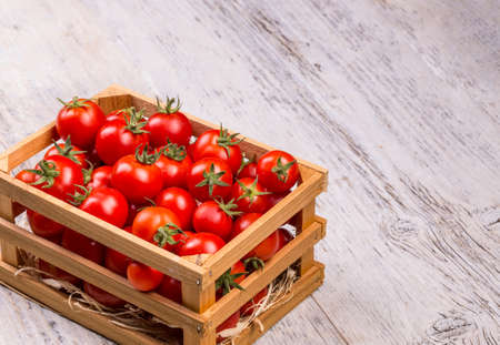 wooden crate: Fresh italian cherry tomatoes on the vine in a wooden crate