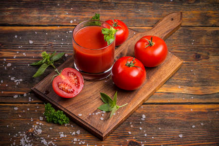 juice fresh vegetables: Glass of fresh tomato juice and tomatoes on a wooden cutting board