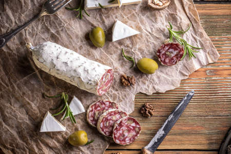 air dried salami: Air dried salami with walnut on old crumpled paper