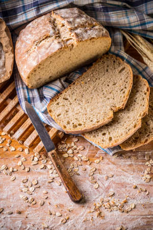 bakery products: Fresh bread and wheat on the wooden background