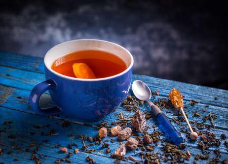 taza de te: Taza con t� negro en el fondo de madera azul