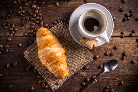 croissant: Coffee and croissant on wooden background