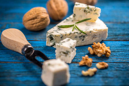 stilton: Blue cheese with nut on blue wooden table