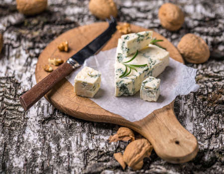 gorgonzola: Gorgonzola cheese on wooden cutting board