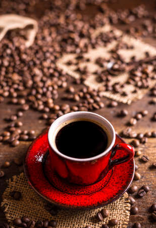 seeds coffee: Cup of black coffee and coffee beans on wooden background