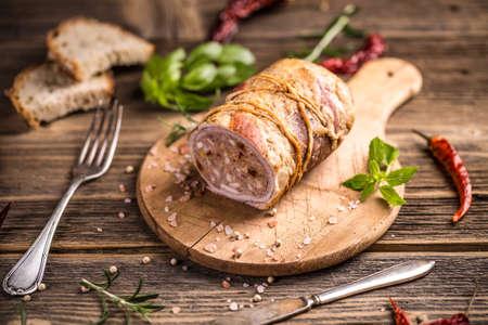 Stuffed meat roll on wooden cutting board