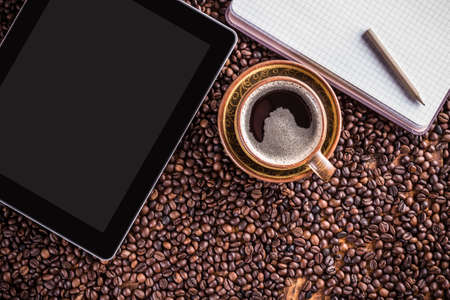 caffee: Digital tablet, note paper and coffee cup on coffee beans background Stock Photo