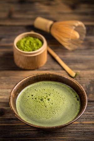 maccha: Organic green matcha tea in a bowl on wooden background
