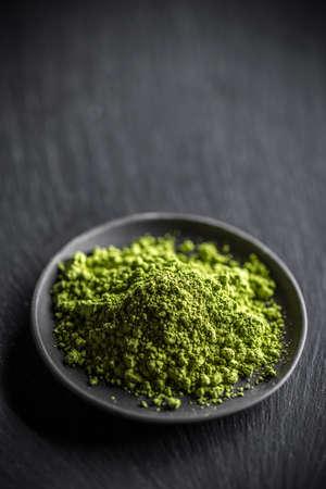 Powder green tea, matcha in black plate Standard-Bild