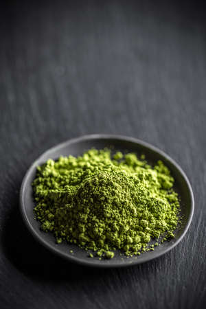 dry powder: Powder green tea, matcha in black plate Stock Photo