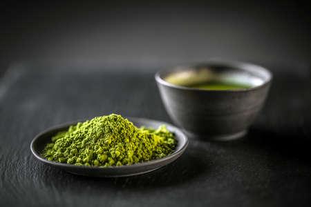 Matcha, powder green tea in black plate Stockfoto