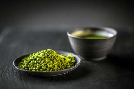 Matcha, powder green tea in black plate Imagens