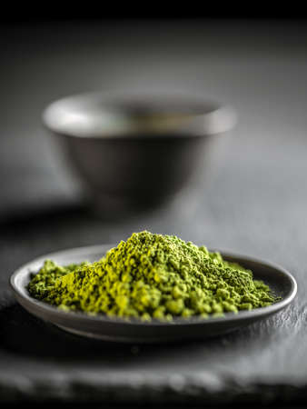green powder: Macha green powder in a plate on black background