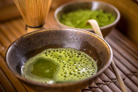 maccha: Green tea matcha in a bowl on vintage wooden surface