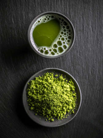 Top view of organic green matcha tea in a bowl and matcha powder