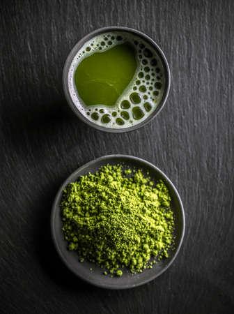 Top view of organic green matcha tea in a bowl and matcha powder