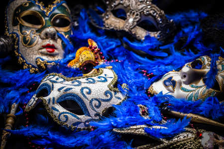 carnivale: A group of venetian, mardi gras mask or disguise on a feather background Stock Photo