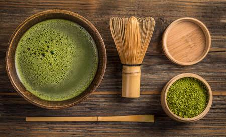 Pohled shora zeleného čaje matcha v misce na dřevěné desce