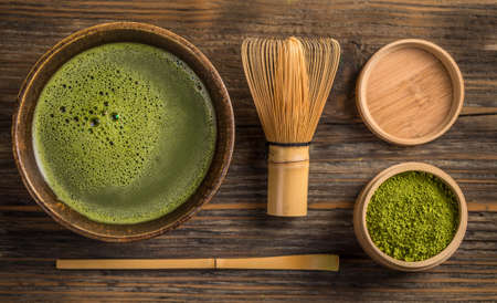 Vista de cima de matcha chá verde em uma bacia na superfície de madeira
