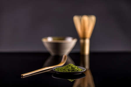 green drink powder: Powdered green tea in plate on black background Stock Photo