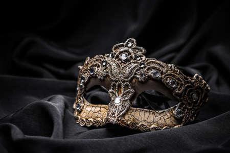 black silk: Brown carnival mask on black silk background