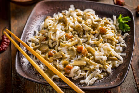 Bowl of noodles with green curry sauce