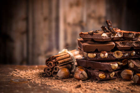 sweet segments: Still life of broken chocolate bar and spices on wooden table Stock Photo