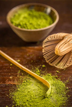 maccha: Raw organic green matcha tea in a bowl with whisk and spoon