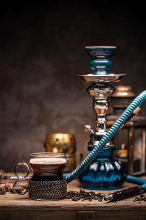 Cup of turkish tea and hookah served in traditional style Archivio Fotografico