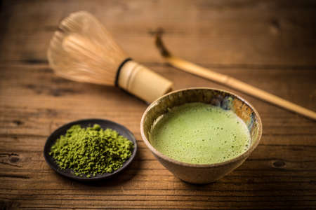 Matcha tea in a tea bowl on wooden background