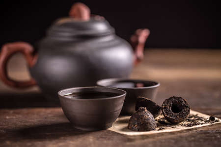pu: Clay teapot and two small cups full of hot pu-erh tea