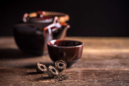 Compressed pu-erh chinese tea on rustic wooden background
