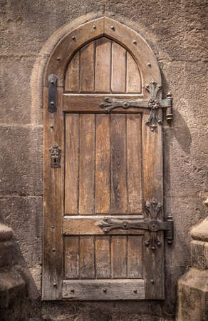 castle wall: Ancient wooden door in stone castle wall Stock Photo