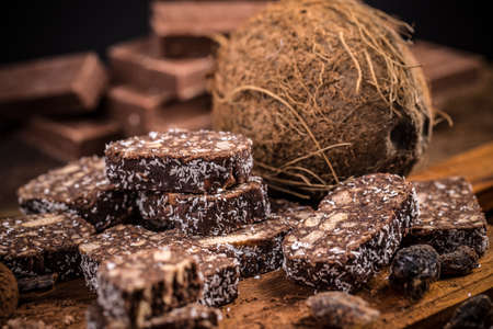 filings: Chocolate dessert, biscuit salami with coconut filings on wooden background Stock Photo