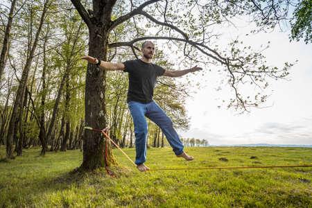 slack: Man slacklining walking and balancing on a rope Stock Photo
