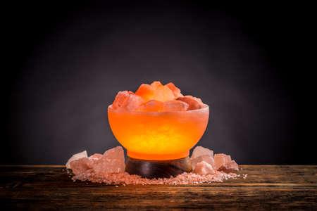 Encendida la lámpara de sal rosa del Himalaya en una mesa de madera