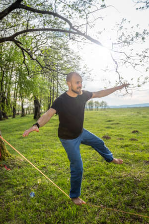 dynamic activity: Man balancing on slackline in the forest