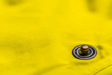 to clasp: Close up of button clasp on yellow jacket